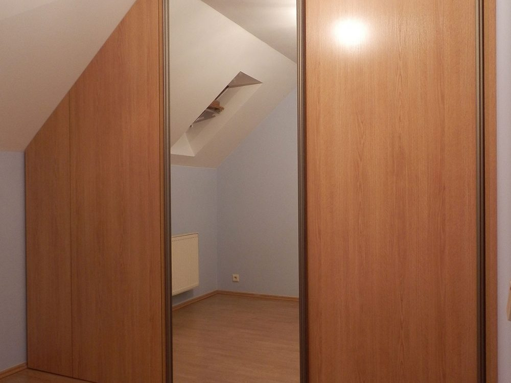 Zabudowa skośnego poddasza - szafa z drzwiami przesuwnymi z lustrem oraz szafka z frontem rozwieranym