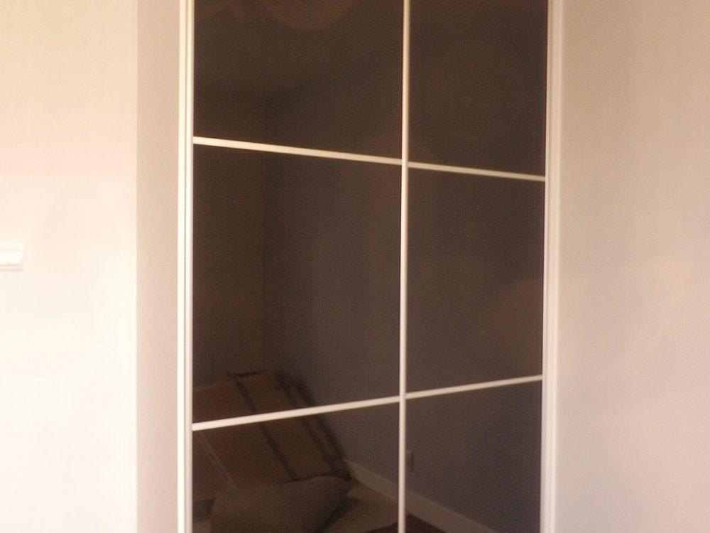 Prosta, elegancka szafa, białe boki, drzwi przesuwne z ciemnym lustrem