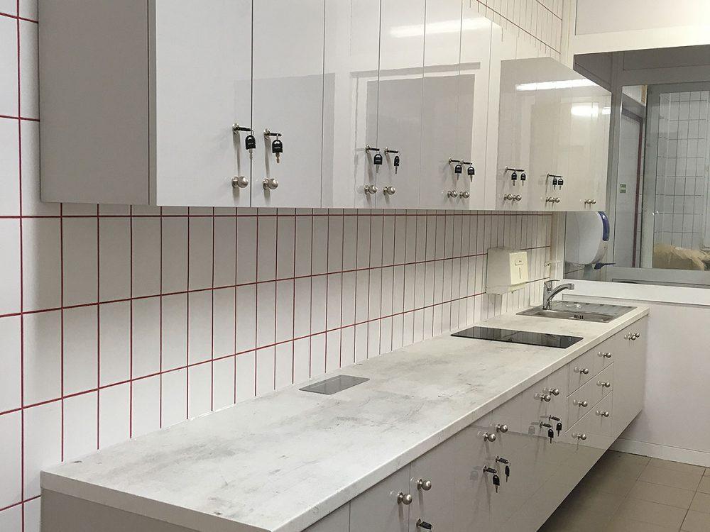 Biała kuchnia pracownicza, szafki zamykane na kluczyk, fronty w połysku