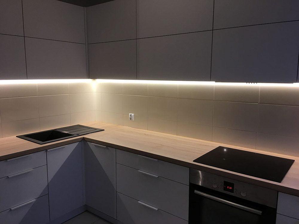 Biała kuchnia typu L, szafki wiszące otwierane do góry (system AVENTOS)