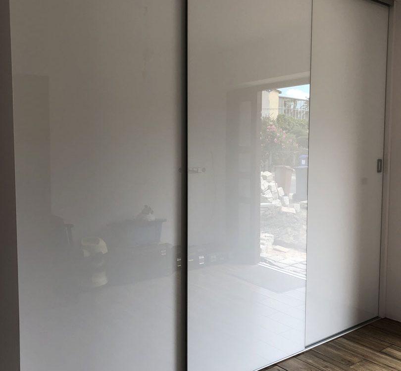 Biała szafa o szerokich drzwiach w okuciach bezramkowych