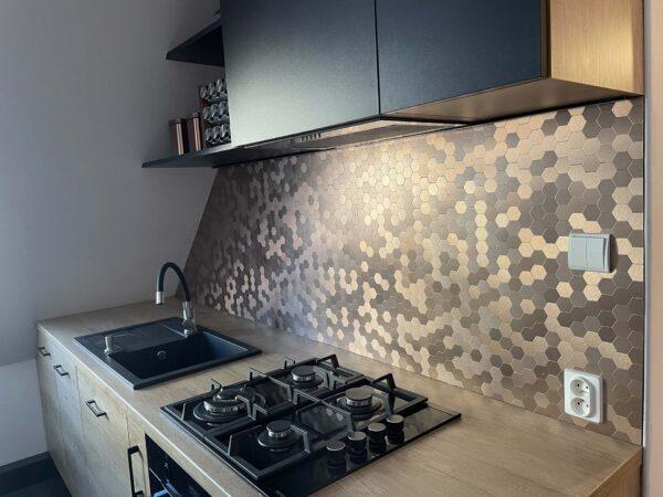 Kuchnia w kolorze drewna, szafki wiszące z frontami w kolorze czarnym